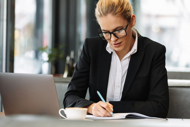 Concentrated business woman writing notes in notebook.