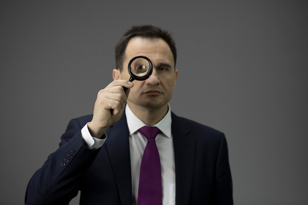 Concentrated businessman looking through loupe, isolated grey background