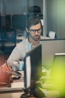 Концентрированный бизнесмен, работающий над дигитайзером в офисе