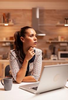 ノートパソコンで夜遅くまで働いている間、家庭の台所に集中した実業家。深夜に最新のテクノロジーを使用して、仕事、ビジネス、忙しい、キャリア、ネットワーク、ライフスタイルのために残業している従業員。