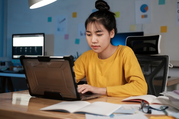 그녀의 노트북으로 늦은 시간에 일하는 집중된 사업가.