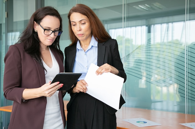 Concentrated businesswomen looking at tablet screen and standing in conference room