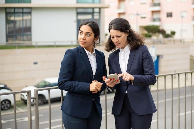 Концентрированные деловые женщины с помощью смартфона