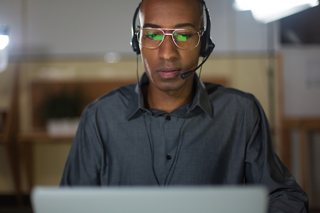 Concentrated call center operator talking with client
