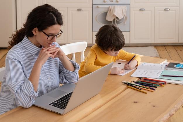集中したカジュアルな実業家が近くの幼い息子のラップトップでビジネスメールを読む