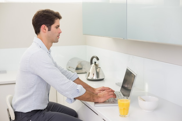 Concentrated casual young man using laptop in kitchen