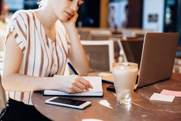 빨간 머리와 주근깨가있는 집중된 백인 여성이 커피 숍에서 컴퓨터를 사용하는 동안 무언가를 쓰고 있습니다.