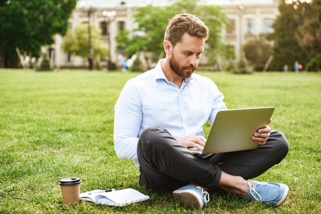Concentrated caucasian man in business clothing, sitting on grass in park with legs crossed while working on silver laptop