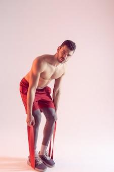 Концентрированный кавказский спортсмен делает упражнения с лентой сопротивления. молодой красивый мускулистый бородатый мужчина с обнаженным спортивным торсом. изолированные на бежевом фоне. студийная съемка. копировать пространство