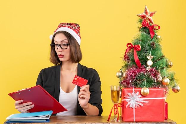 Signora affascinante concentrata in vestito con il cappello e gli occhiali di babbo natale che mostrano la carta di credito nell'ufficio su colore giallo isolato