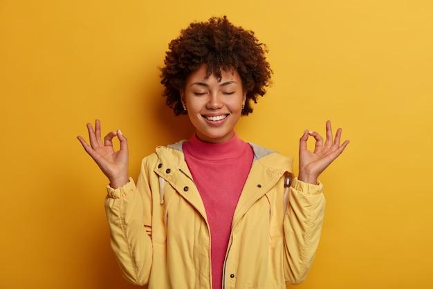 집중된 쾌활한 곱슬 여자는 양손을 괜찮은 몸짓으로 유지하고, 실내 명상을하고, 눈을 감고, 노란색 아노락을 입는다.