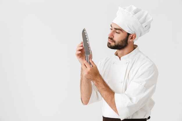 Concentrated chief man in cook uniform holding big sharp metal knife isolated over white wall