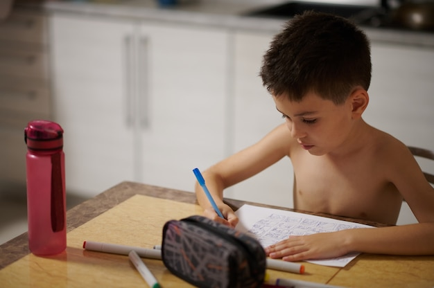 집중된 소년은 백서에 애니메이션 만화를 그립니다. 대리석 테이블에 연필 케이스와 물병