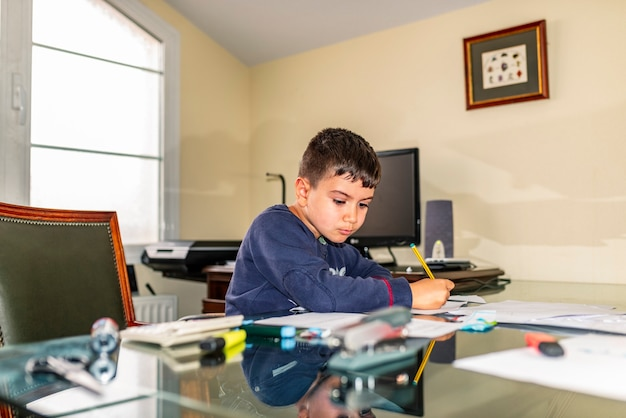 Concentrated child doing homework in daddy's office
