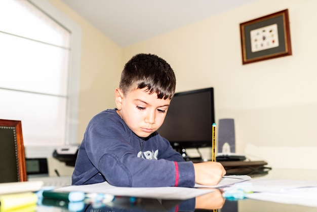 Concentrated child doing homework in daddy's office Premium Photo