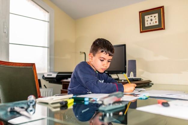 Сосредоточенный ребенок делает домашнее задание в офисе папы