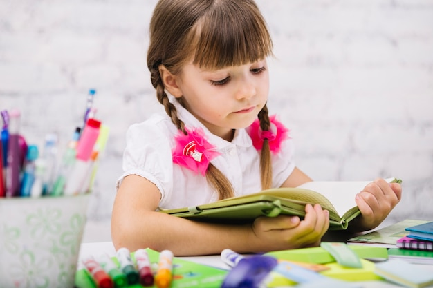 Concentrated child reading book at table