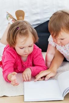 Концентрированные дети, читающие книгу с матерью