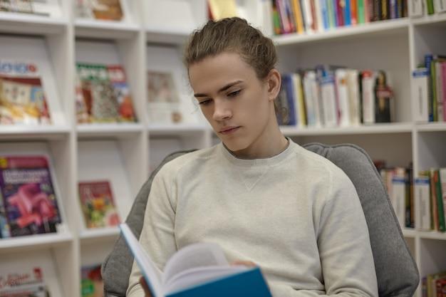 大学の図書館に座って、冒険小説の読書に夢中になっている集中した大学生