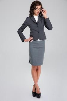 Сосредоточенная уверенная в себе кудрявая симпатичная деловая женщина в очках и сером костюме стоит, скрестив ноги и касаясь своих очков