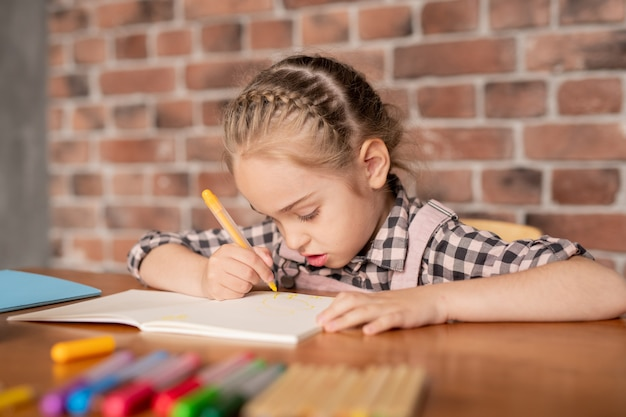 Сосредоточенная творческая девушка с заплетенными волосами сидит за столом и рисует фломастером в блокноте дома