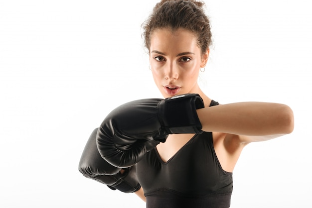 Concentrated curly brunette fitness woman trains in boxing gloves