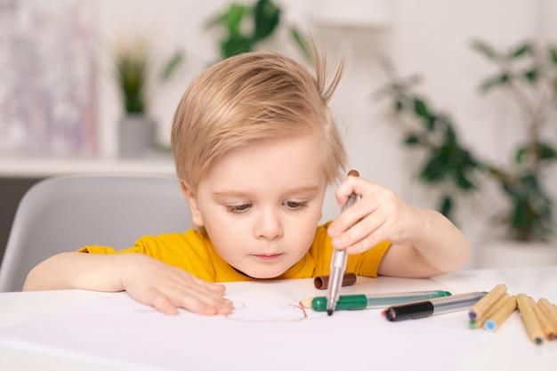 집중된 귀여운 blond-haired 소년 테이블에 앉아 다채로운 펠트 펜으로 종이에 그리기