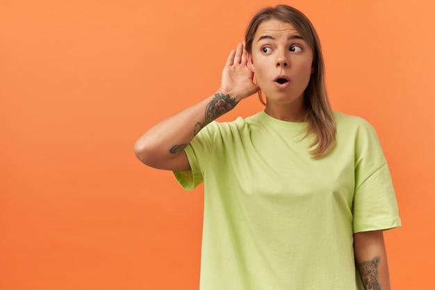 黄色いtシャツを着たかわいい若い女性が集中して耳の近くに手を置き、オレンジ色の壁越しに遠く離れた音を聴こうとする