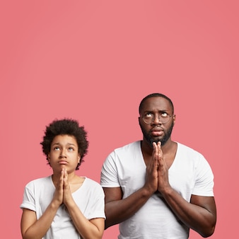 Concentrated dad and son pose together against pink studio wall, keep hands in praying gesture, believe in something good