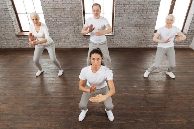 筋肉を緊張させながら肘を曲げて手を握っている白いtシャツを着ている集中した黒髪の男