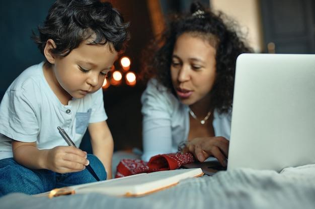 Concentrated dark skinned little boy learning alphabet, writing down letters in copybook, sitting on bed with his young mother using portable computer for remote work.