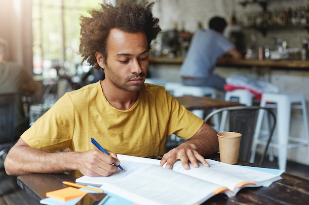 Concentrated dark-skinned male with african hairstyle and bristle wearing casual clothes writing notes in copybook and reading books while sitting at wooden table in cafeteria and drinking coffee.