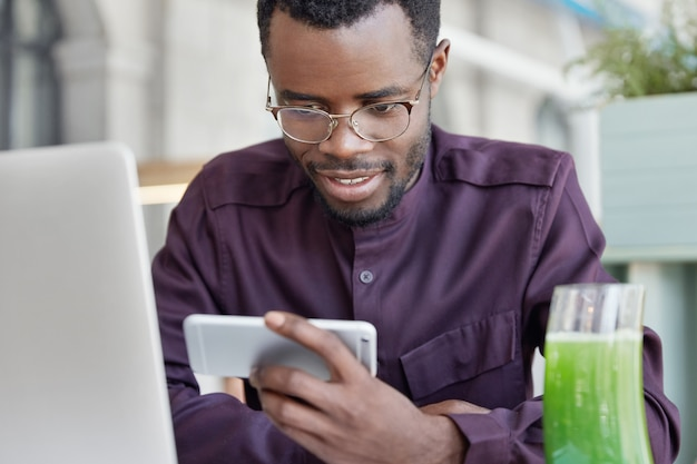 Concentrated delighted african american student watches movie or video on smart phone, wears formal clothes and round glasses