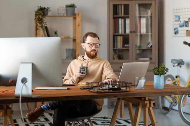 홈 오피스의 나무 테이블에 앉아 커피를 마시면서 컴퓨터를 사용하는 안경에 집중된 디자인 프리랜서