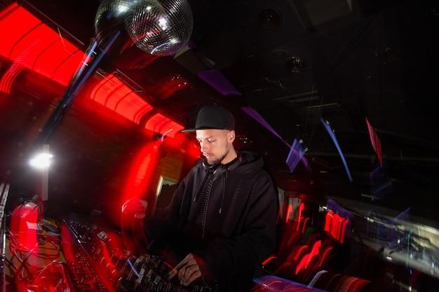 集中djがパーティーで音楽を演奏します。黒い帽子とカジュアルな黒い服を着た格好良い若い男は、音楽をミックスするためにターンテーブルを使用しています。赤い光でぼやけた背景。