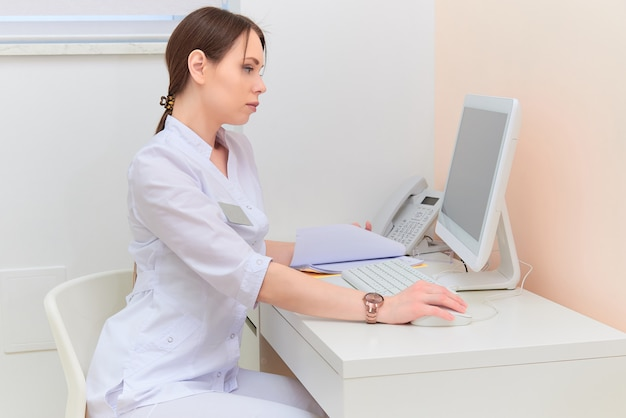 Concentrated doctor with report looking at computer monitor at desk in medical office.