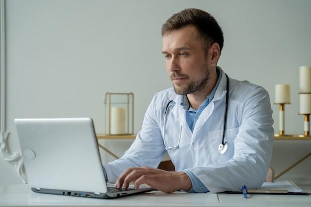Сосредоточенный врач, работающий с ноутбуком на столе в офисе, мужчина-врач, использующий ноутбук на столе в клинике