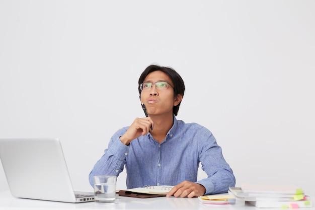 ノートブックに書き込み、白い壁の上のテーブルで考えているラップトップで作業している集中疑わしいアジアの若いビジネスマン