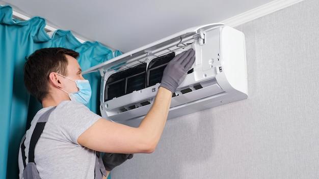 Сосредоточенный электрик в футболке и маске чистит потолочный кондиционер белой тканью при обслуживании занавесками в комнате крупным планом