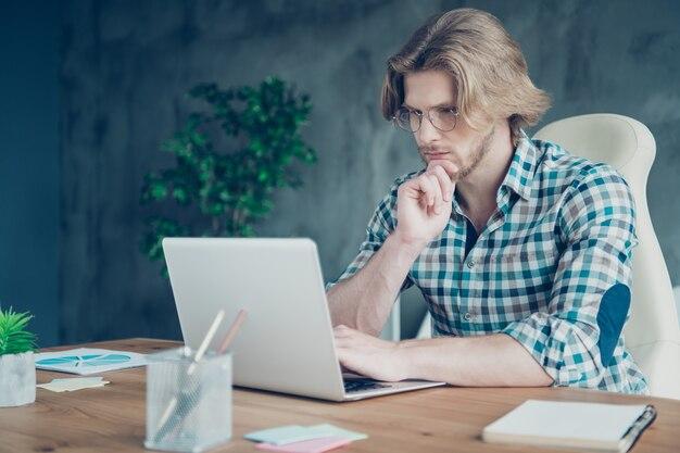 Сосредоточенный сотрудник, работающий в офисе на ноутбуке