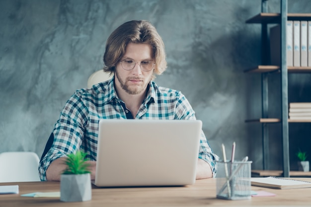 Concentrated employee working in the office on laptop