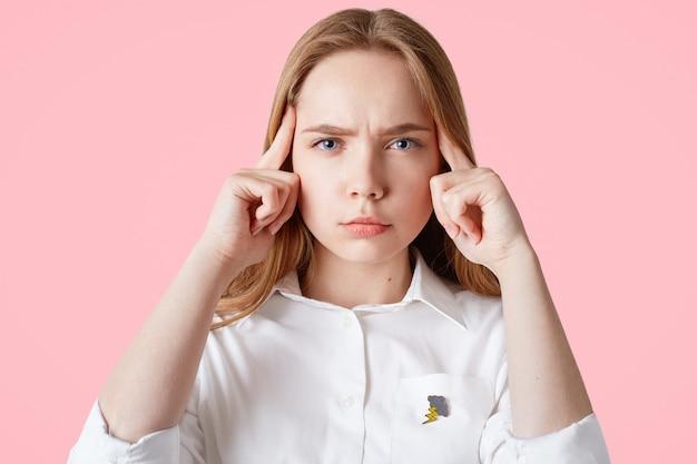 集中されたヨーロッパの女性モデルは、ピンクに分離された寺院に人差し指を保ちます。真面目な女子学生が必要な情報を思い出そうとする