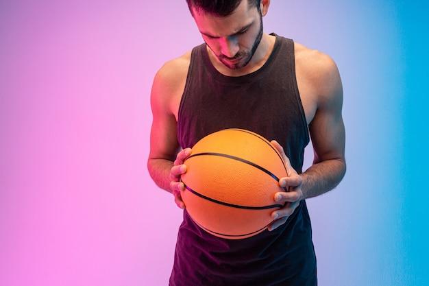 集中したヨーロッパ人がバスケットボールのボールを手に持っています。若いひげを生やした男はタンクトップを着て見下ろしています。青とピンクの背景に分離。スタジオ撮影。コピースペース