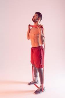 Концентрированный европейский спортсмен выполняет упражнения с лентой сопротивления. молодой красивый бородатый мужчина с обнаженным спортивным торсом. изолированные на бежевом фоне. студийная съемка. копировать пространство