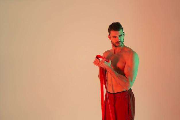 Сосредоточенный европейский спортсмен делает упражнения с лентой сопротивления. молодой красивый бородатый мужчина с обнаженным спортивным торсом. изолированные на бежевом фоне с зеленым светом. студийная съемка. копировать пространство