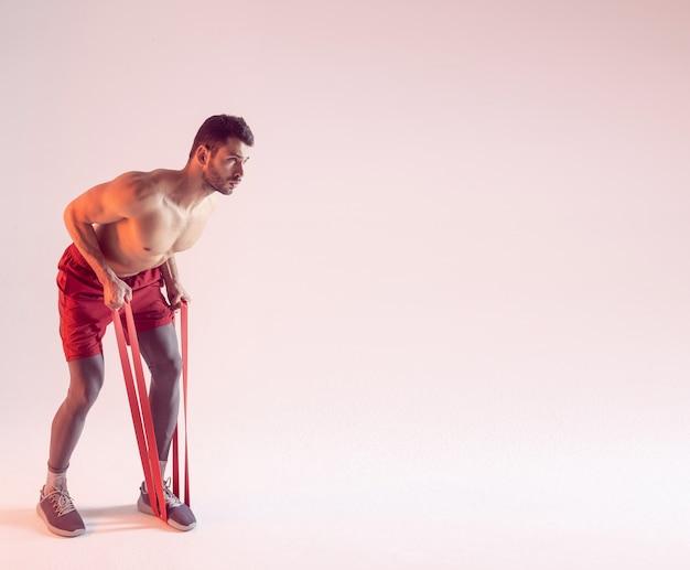 Концентрированный европейский спортсмен выполняет упражнения с лентой сопротивления. молодой красивый мускулистый бородатый мужчина с обнаженным спортивным торсом. изолированные на бежевом фоне. студийная съемка. копировать пространство