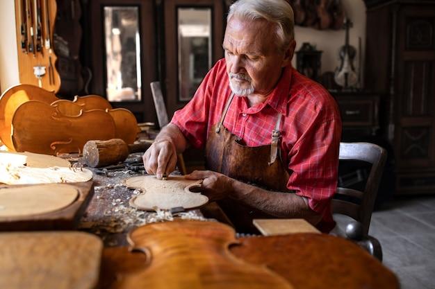 Сосредоточенный опытный старший плотник работает над своим творческим проектом в столярной мастерской.
