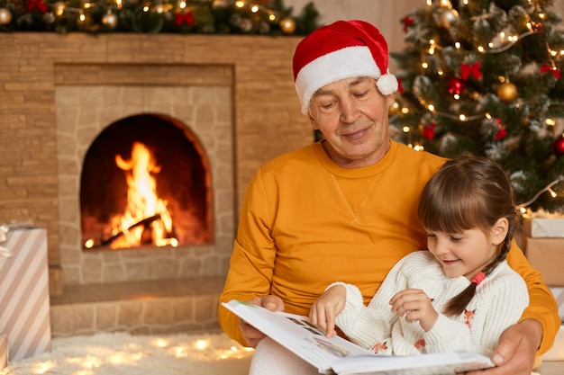Concentrated family sitting on floor in living room and read fairytale and looking at pictures, spending time together on christmas eve, senior man wearing santa claus hat, grandad and granddaughter.