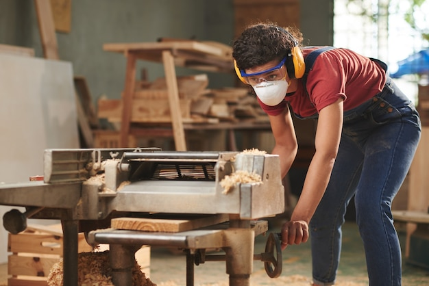 Concentrated female carpenter in mask, safety glasses and earmuffs processing wooden board on woodworking machine