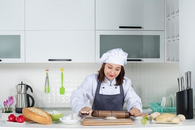 Chef commis femminile concentrato in uniforme in piedi dietro il tavolo che prepara la pasticceria nella cucina bianca